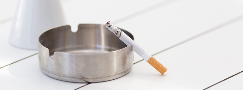 Burning cigarette in metal ashtray on white table in cafe